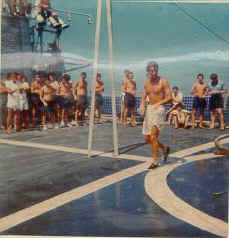 Flight deck of HMS Jupiter.  HRH undergoing his ordeal during a cross-the-line ceremony.  He has just survived a custard pie in his face - amongst other things!