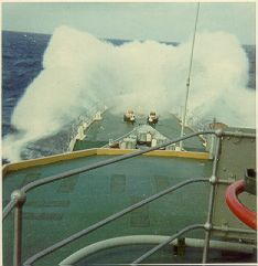 Heavy weather. The sea crashing over HMS Jupiters bow in the Pacific Ocean.